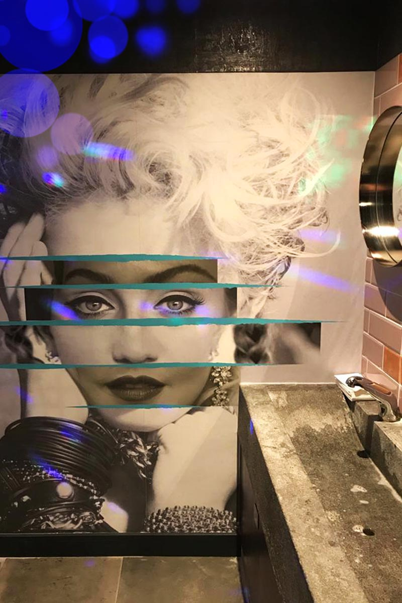 Interior bathroom photograph showing sinks with a wall graphic behind of Madonnas face