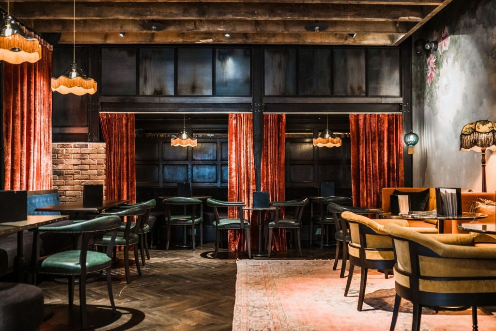 Velvet curtains and vintage light fittings at The Gun Pub, Spitalfields London Sourced by Ct Creative
