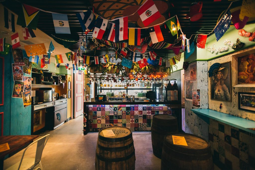 Casa Bonita pop-up bar in London. Eclectic interior with hanging flags and coloured walls designed by CT Creative